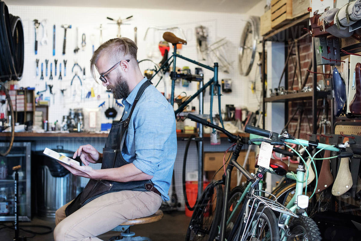 A man working in a bicycle repair shop, seated using a digital tablet   stock photo