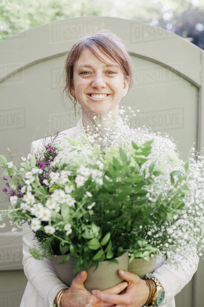 Portrait Of A Smiling Woman Carrying A Bunch Of White Flowers