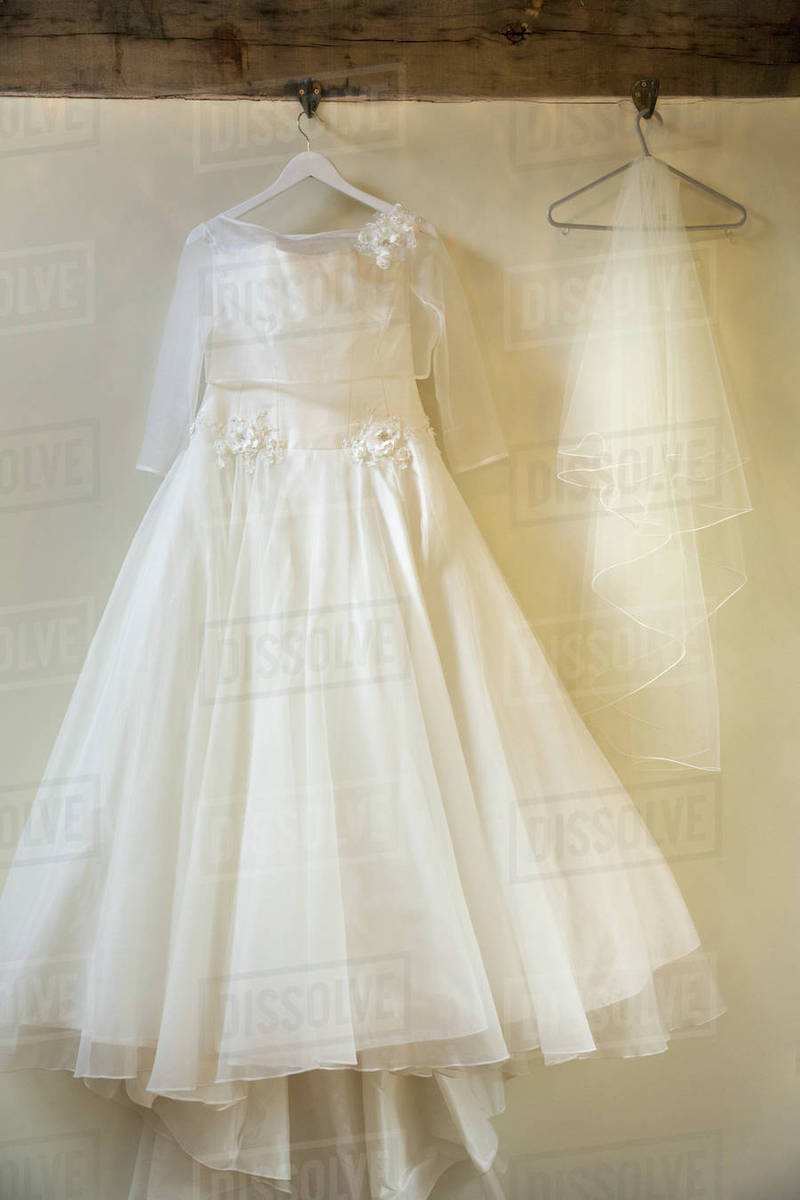 A Long White Wedding Dress With Full Skirt Petticoats And Veil On A