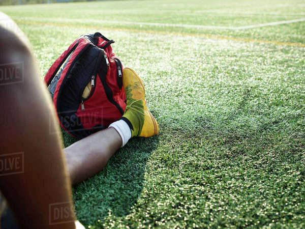 Boy wearing yellow sport shoe sitting on a lawn, a backpack at this feet. Royalty-free stock photo