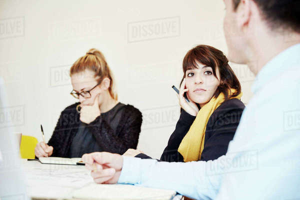 Three people seated at a business meeting, two woman and a man. Royalty-free stock photo