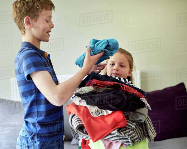 A boy sorting laundry and piling it up in the arms of a young girl.  Royalty-free stock photo