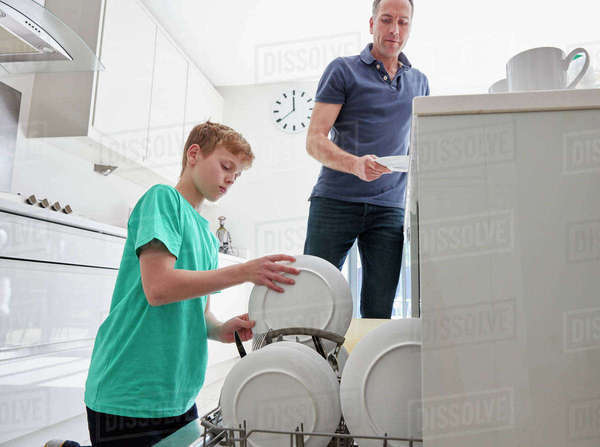 A family home. A man and a boy putting plates in the dishwasher in a kitchen.  Royalty-free stock photo