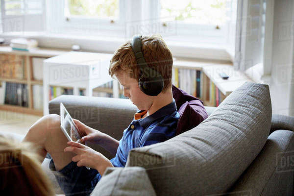 A family home. A boy on a sofa, using a digital tablet, wearing headphones.  Royalty-free stock photo