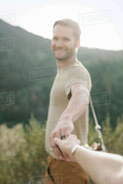 A man holding out his hand to a companion. Royalty-free stock photo