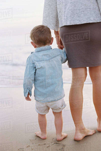 Woman standing on a sandy beach by the ocean, holding her young son's hand. Royalty-free stock photo