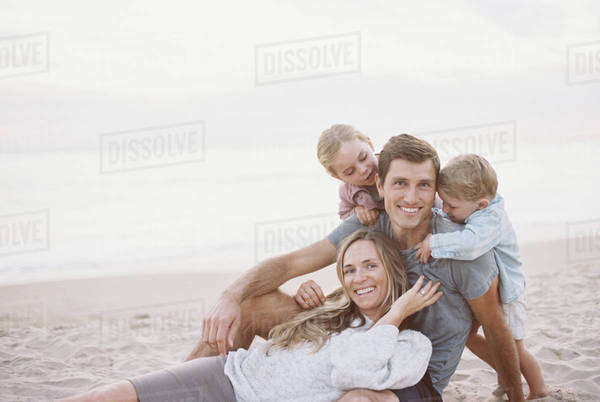 Embracing couple with their son and daughter on a sandy beach, looking at camera, smiling. Royalty-free stock photo