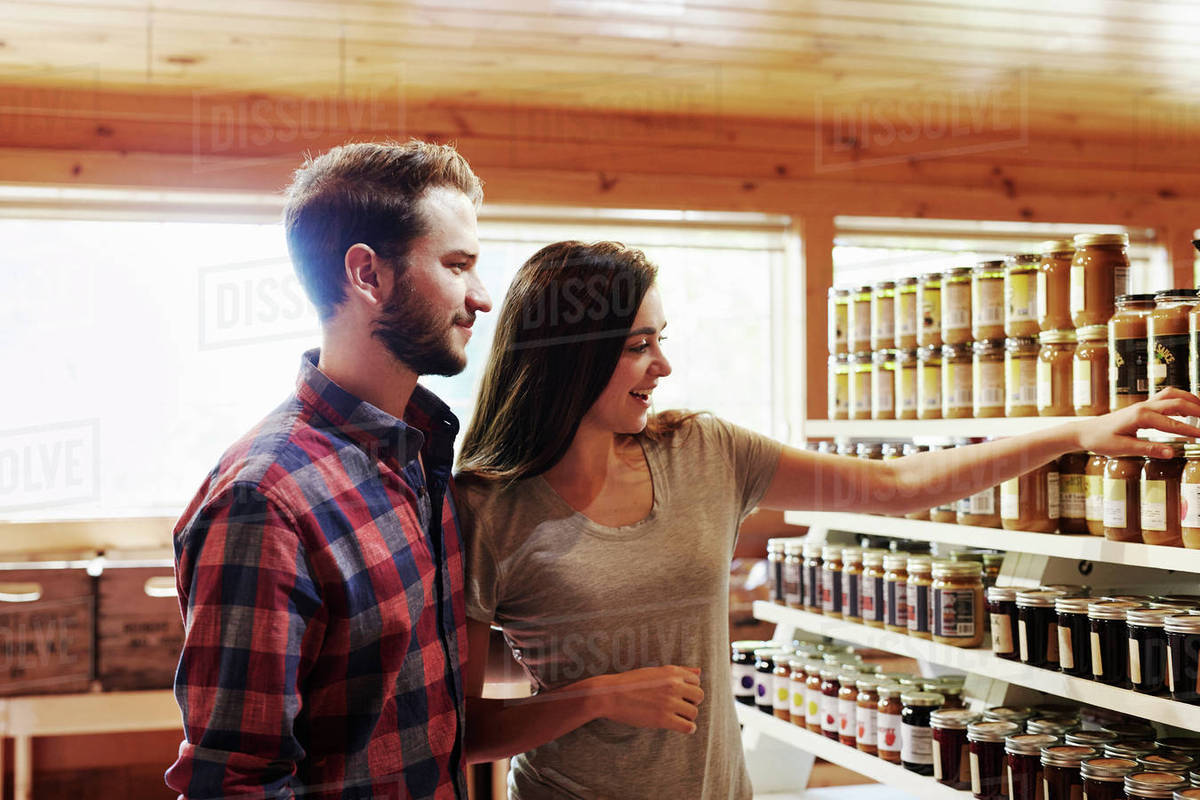 eee3739116 A young man and woman choosing from a display of canned produce in a farm  shop.