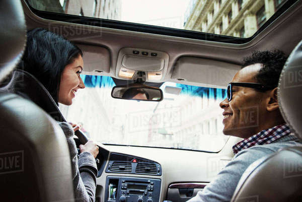 A young woman and young man in a car looking at each other and smiling, seen from the back seat. Royalty-free stock photo