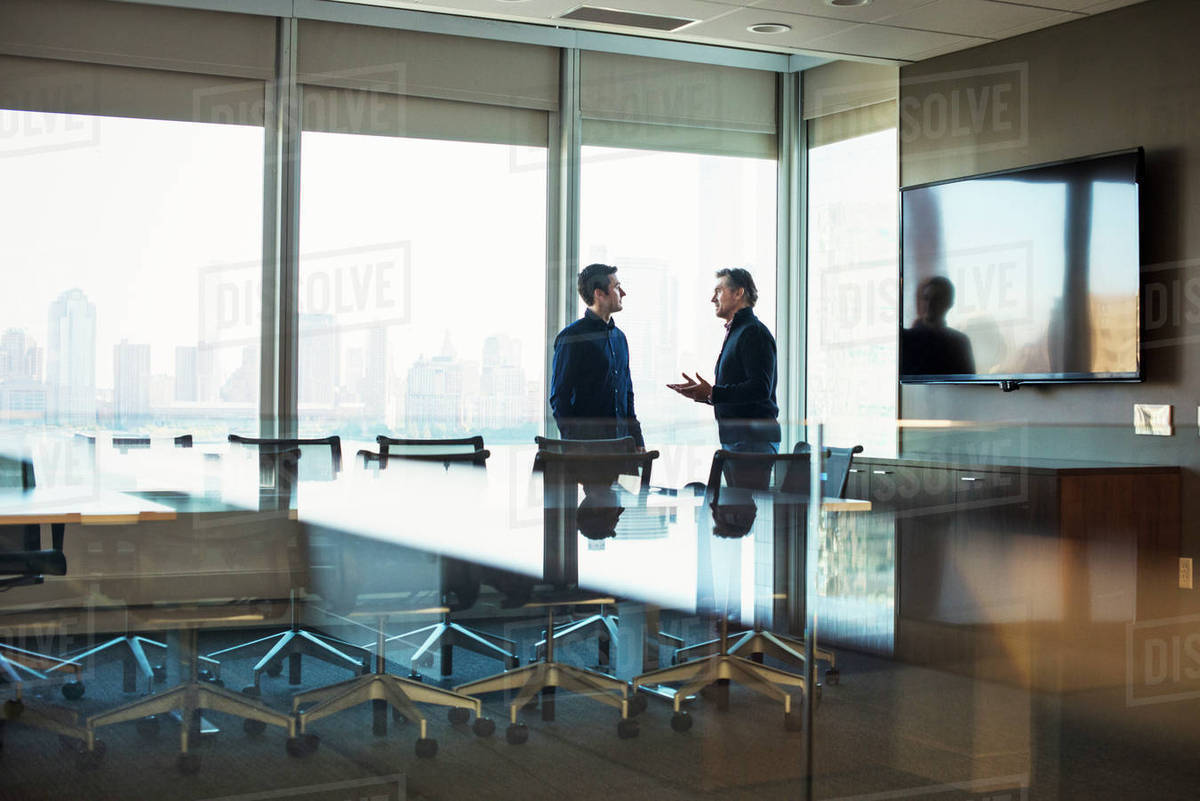 Two Men Standing At A Table In A Meeting Room Talking To Each Other - Standing conference room table