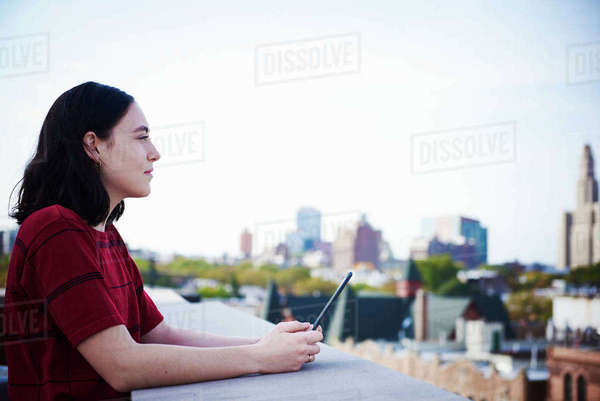 A young woman standing on a rooftop holding a tablet. Royalty-free stock photo