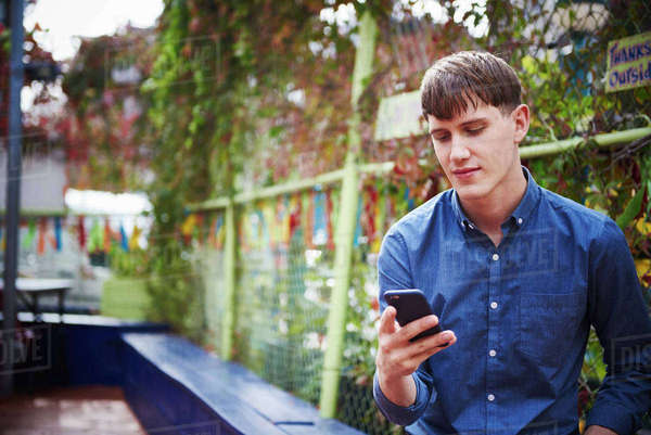 A young man sitting outdoors looking down at a cellphone. Royalty-free stock photo