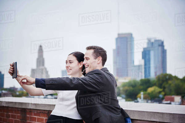A young woman and a young man standing on a rooftop looking at a cellphone together. Royalty-free stock photo