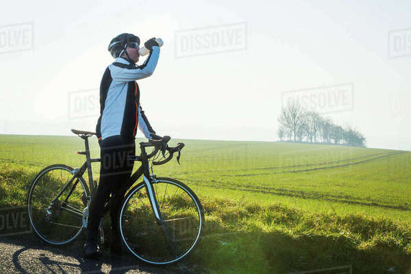 A cyclist by the side of a road, having a break and drinking from his water bottle.  Royalty-free stock photo