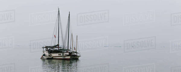 A boat sailing in open water in foggy conditions. Royalty-free stock photo