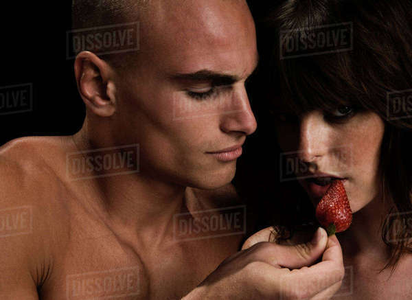 Nude couple, man feeding woman with strawberry. Royalty-free stock photo