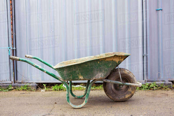 Green wheelbarrow on a building site in front of a metal container. Royalty-free stock photo