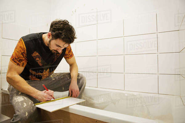 A builder, tiler working in a bathroom, marking a tile with a pencil. Royalty-free stock photo