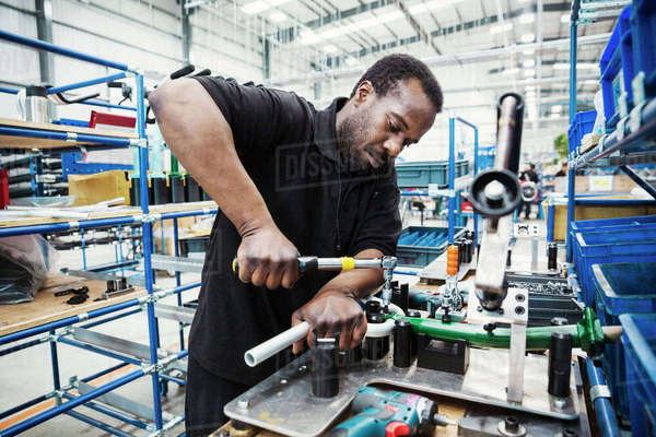 Male skilled factory worker, a man holding a tool, working to assemble parts of a bicycle in a factory.  Royalty-free stock photo