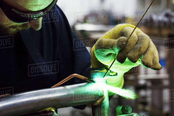 Male skilled factory worker using tools to weld and solder parts of a bicycle in a factory.  Royalty-free stock photo