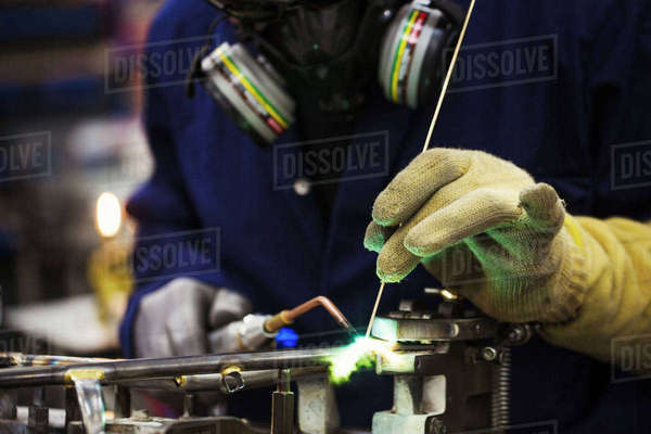 Close up of skilled factory worker welding metal parts of a bicycle in a factory. Royalty-free stock photo