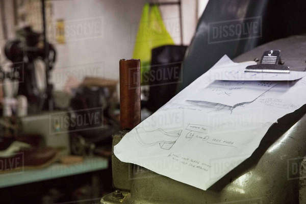 Close up of handwritten notes and drawings on a clipboard in a shoemaker's workshop. Royalty-free stock photo