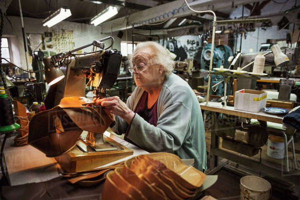 Older woman sitting at a sewing machine in a shoemaker's workshop. Royalty-free stock photo