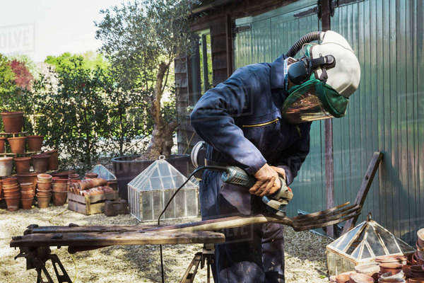 Man standing outdoors, wearing a face mask, working on a metal pitchfork with an angle grinder. Royalty-free stock photo