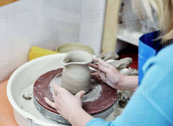 A woman using a pottery wheel, placing a small moulded thrown object, a jug with a handle in the centre of the wheel circle.  Royalty-free stock photo