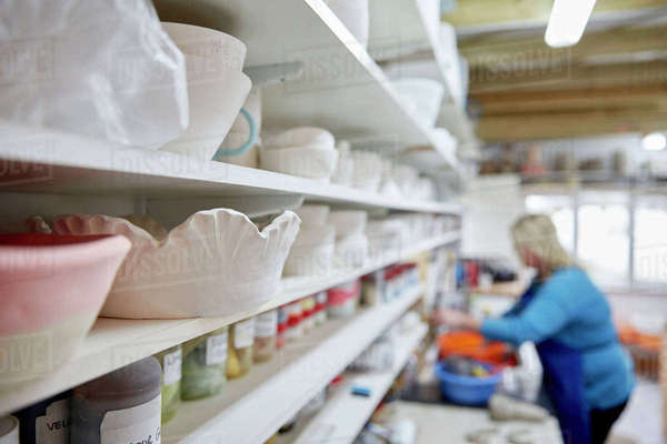 A woman working at a bench in a pottery studio. Shelves storing pots and bowls.  Royalty-free stock photo