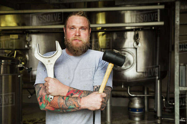 Man standing in a brewery, holding a mallet and a large metal wrench. Royalty-free stock photo