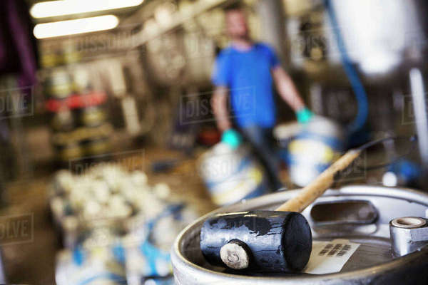 Close-up of a mallet lying on a metal beer keg in a brewery. Royalty-free stock photo