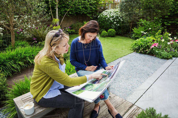 Two women sitting on a bench in a garden, looking at a portfolio with gardening images, discussing garden design. Royalty-free stock photo