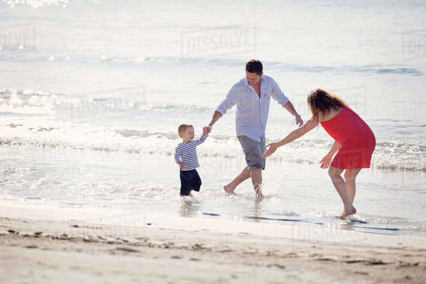 Woman wearing red dress and man wearing shorts standing on a sandy beach by the ocean, playing with young boy. Royalty-free stock photo