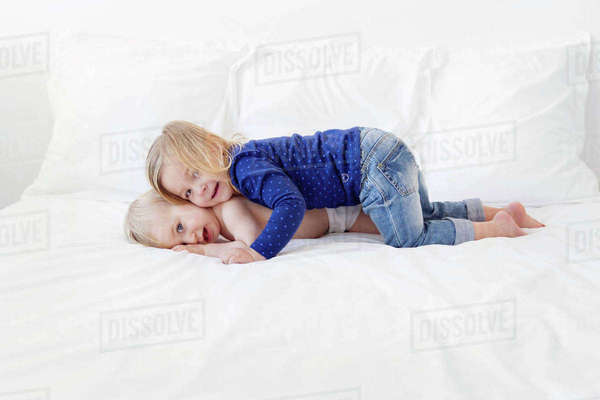 Girl with blond hair wearing jeans and blue top lying on top of baby boy on a bed, hugging. Royalty-free stock photo