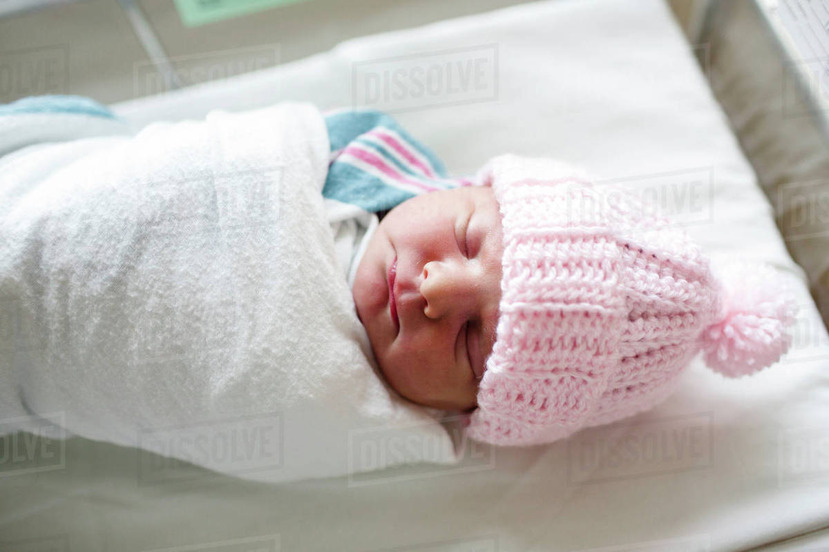 High angle close up of newborn baby wearing pink knit hat lying on her back  in hospital crib. 13d70ba60740