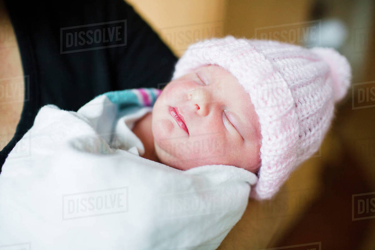 Close up of woman holding newborn baby wearing pink knit hat ... ef11a64e02c2
