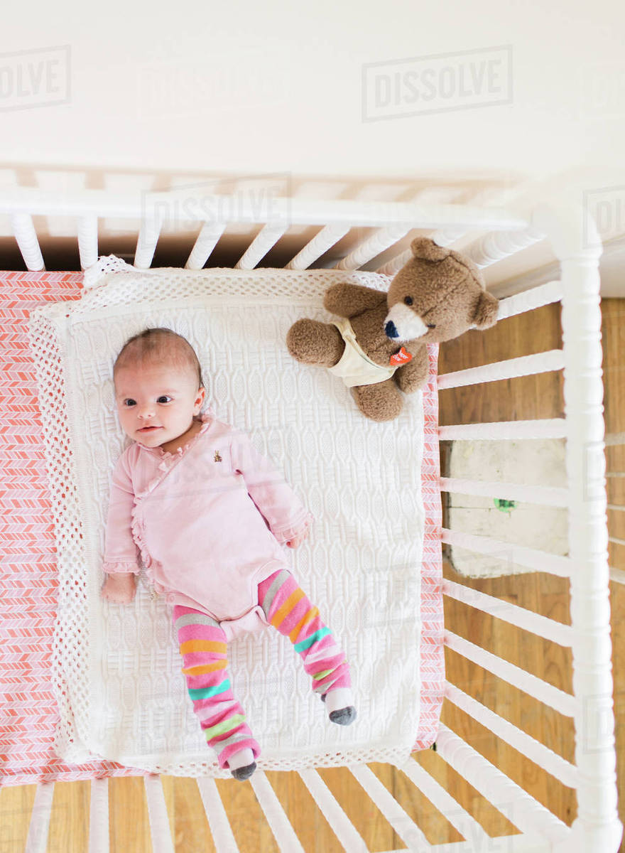 b36e8f13234e Baby wearing pink onesie lying on her back in a white crib. - Stock ...