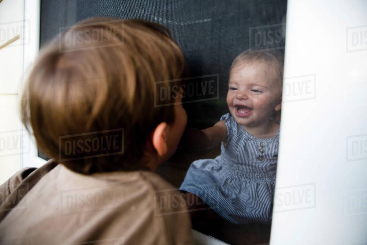 Boy Child Looking Through A Screen Door At A Baby Girl Inside A
