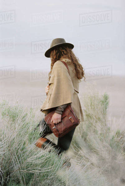 Woman walking across a flat scrub landscape, wearing a hat and carrying a leather bag. Royalty-free stock photo