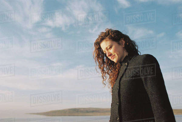 Woman with brown, long and curly hair standing on the shore of a lake. Royalty-free stock photo