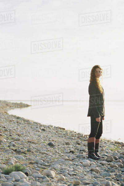 A woman standing on the shore of a lake. Royalty-free stock photo