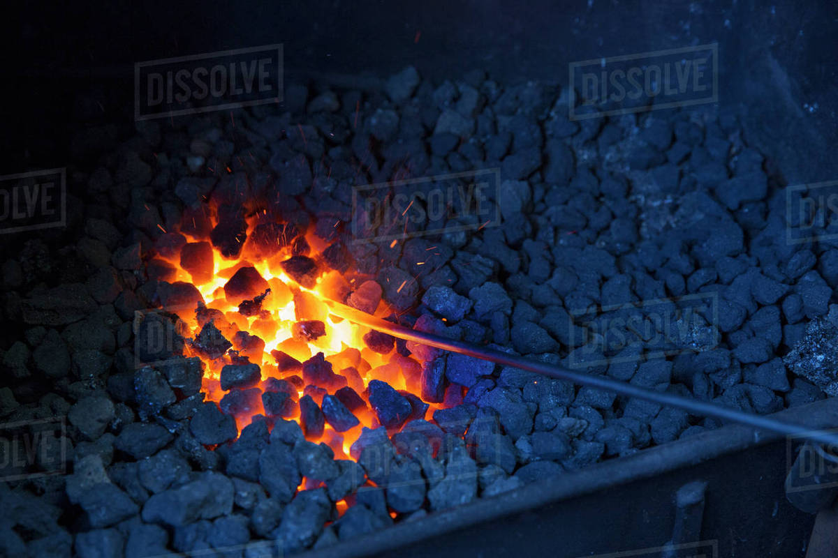 A glowing metal rod in the hot coals in a blacksmith's forge  stock photo