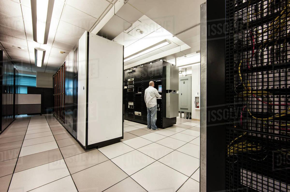 computer server room racks with technician in background stock