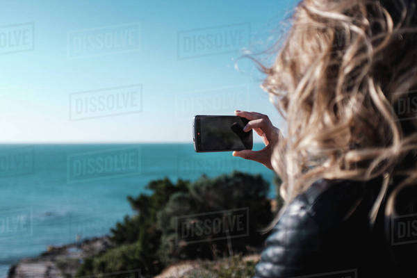 Young woman taking a picture on a coast Royalty-free stock photo