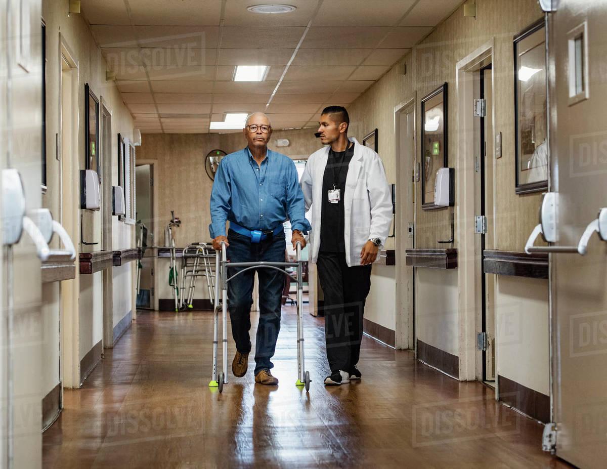 Male nurse assisting senior man walking down corridor with mobility walker Royalty-free stock photo