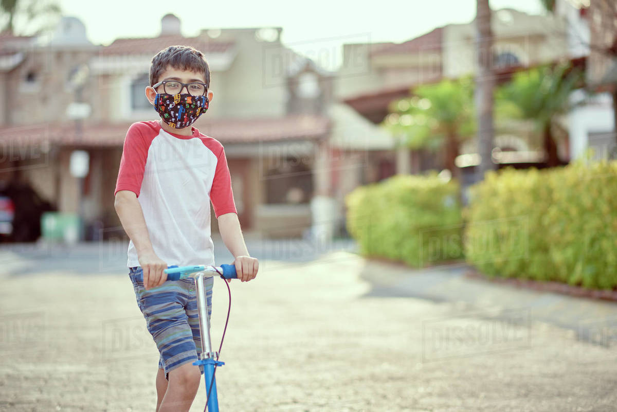 Mexico, Zapopan, Boy with face mask riding scooter Royalty-free stock photo