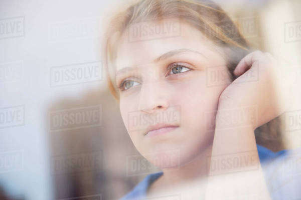 Portrait of teenage girl (12-13) looking through window Royalty-free stock photo