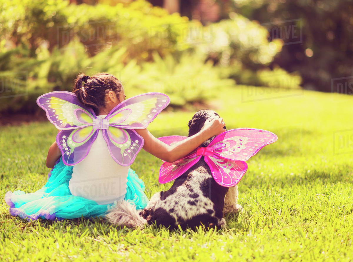 Rear view of girl (8-9) wearing fairy costume stroking dog Royalty-free stock photo