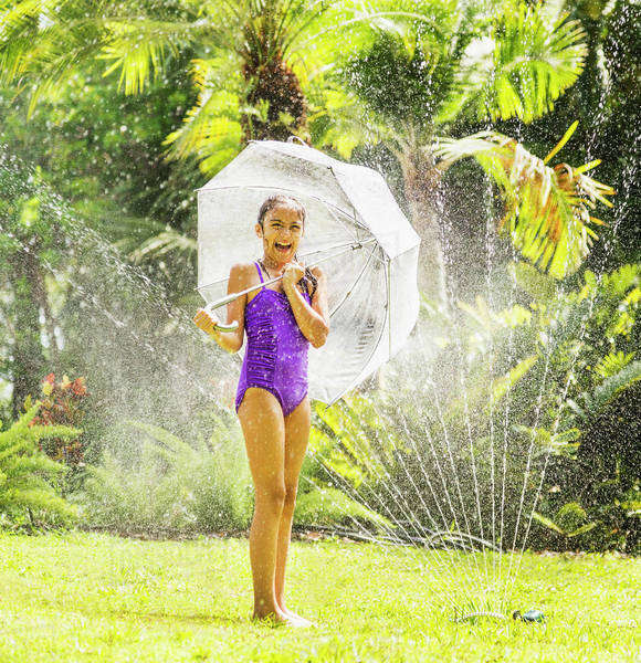 Girl (8-9) playing in sprinkler Royalty-free stock photo